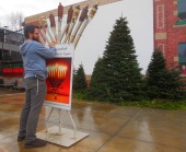 Rabbi Avremi Yamush putting up a poster for Festival of Lights
