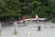 Children playing on a driftwood teeter-totter.